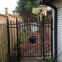 Iron Gate Between Wood Fence & House